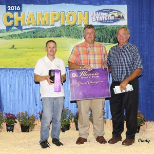 Adrian Buff holding the Grand Champion, Vermilion River Blue with George Obernagle and Joe Hamilton, who purchased the cheese.